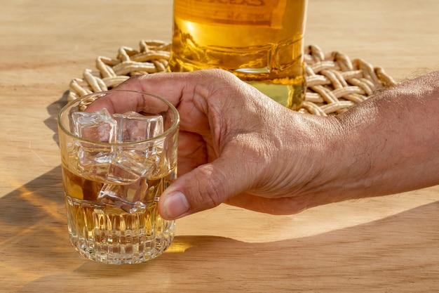 手は飲酒をやめるためにウイスキーのグラスをチェーンに固定します。アルコール依存症の概念。アルコール依存症の飲み物をやめなさい。
