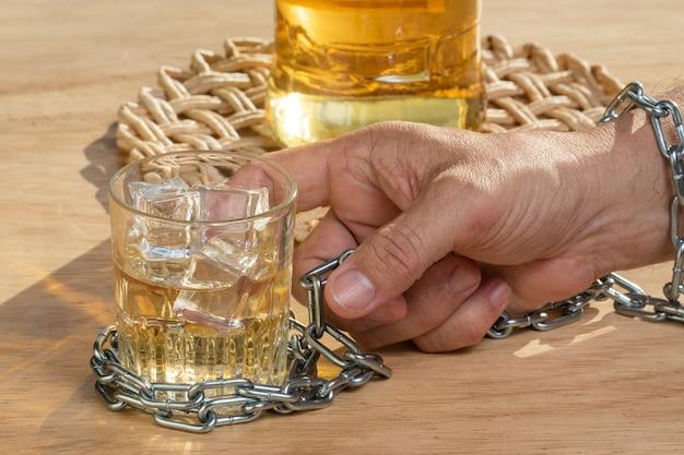 Руки фиксируют цепочку стакана виски, чтобы бросить пить. концепция алкоголизма. прекратить алкогольную зависимость пить.