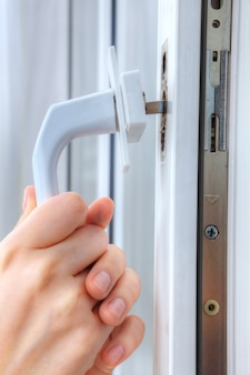 Hands locksmith  remove handle of window frame, close-up.