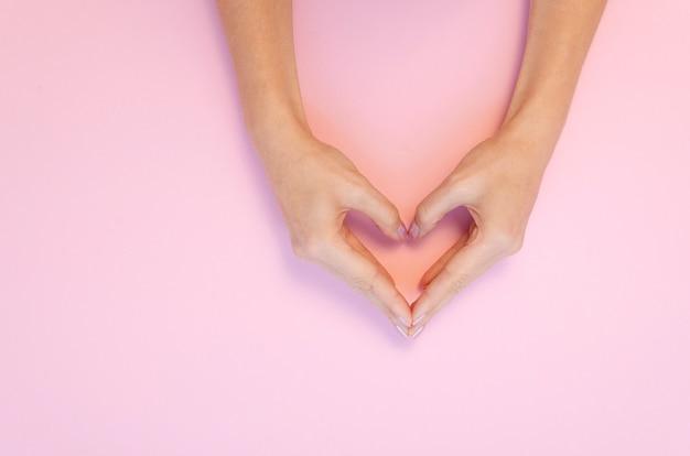 手はピンクの表面にハート形のジェスチャーを作る