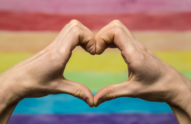 Hands make a heart sign against the background of the rainbow flag. The concept of LGBT