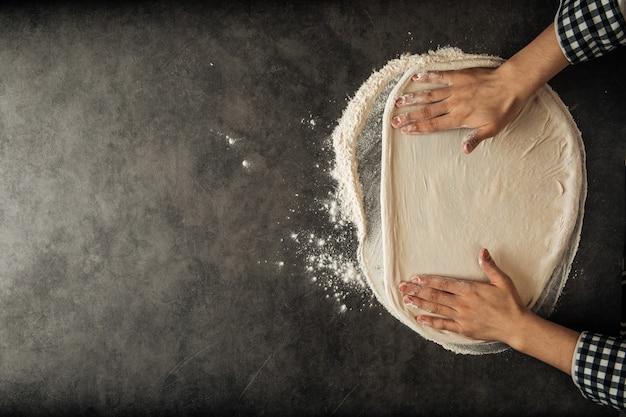 小麦粉の背景を持つピザ生地を作る手