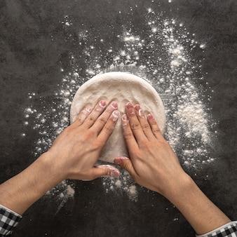 Руки, делая тесто для пиццы с мукой