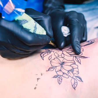 Hands making flower tattoo with needle