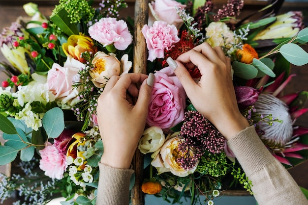 Руки делают букет композиции цветов