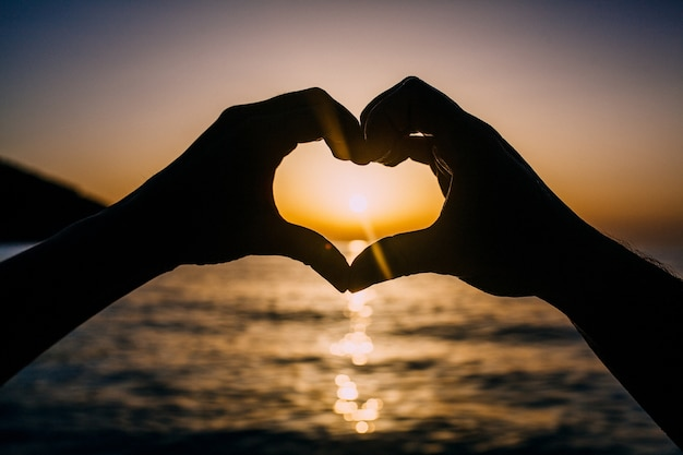 Hands making heart shape on sunset background at sea