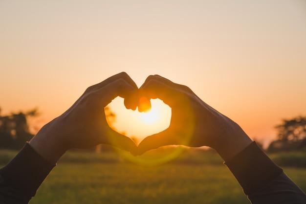 Руки, делающие форму сердца с закатом.