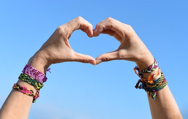 Hands making heart symbol on sky background friendship bracelets on wrists