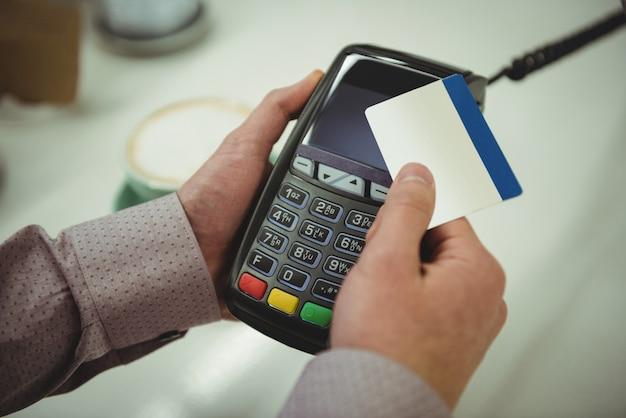 カフェでクレジットカードを介して支払いを行う手カフェでクレジットカードを介して支払いを行う手