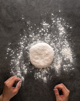 Hands making a pizza dough with flour