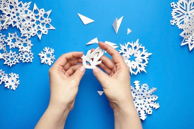 Руки делают снежинку из белой бумаги на синем