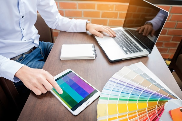 Hands of male hipster modern graphic designer in office working with colour samples. man at workplace choosing colour swatches, closeup. creative people concept.