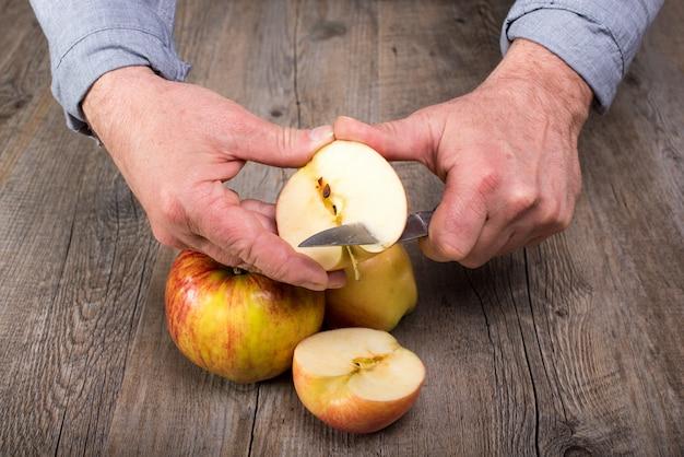 Hands of a man cutting an apple