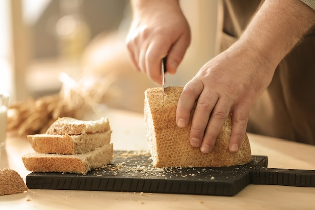 Hands of man cutting bread on kitchen table
