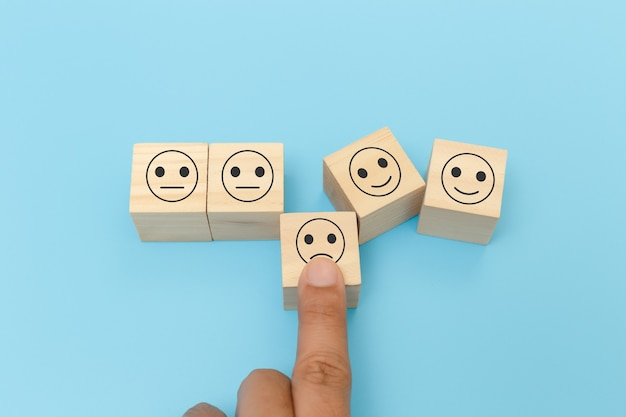 Hands of man finger pointing selection wooden cube blocks with unhappy emotion icons blue background. personnel not selected of corporate. rating and ranking business concept.