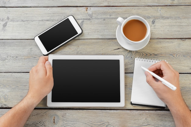 Hands of a man holding blank tablet device over a wooden workspace table
