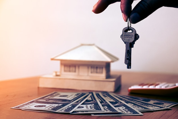 Hands man holding house keys with money and small house on wooden table.