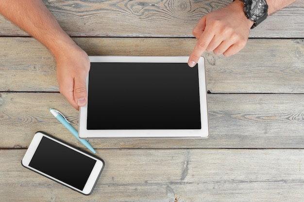Hands of a man holding tablet device over a wooden workspace table