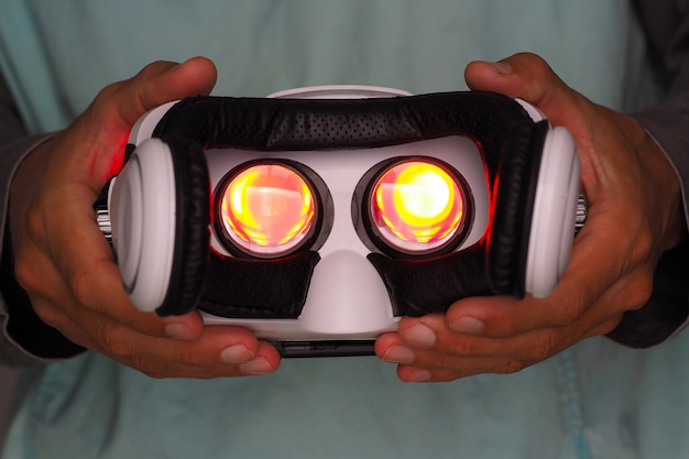 Hands of man holding virtual reality goggles. red light inside.