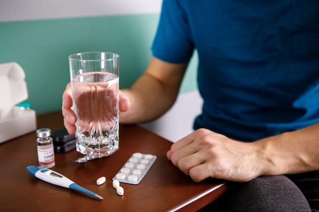 Руки человека, держащего таблетку и стакан воды над столом, сидя на диване и собираясь принимать лекарство