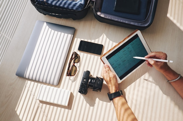 Hands of man looking at business calendar on tablet, and suitcase with electronic devices nearby
