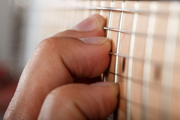 Hands of man playing electric guitar. fingers pressing strings closeup. macro