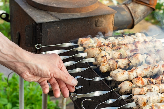 Hands of man prepares barbecue meat on skewer by grill on fire outdoors