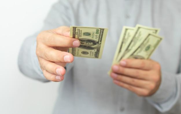 Hands of man proposing money us dollar bills to you close-up