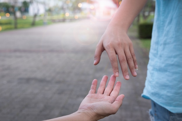 Hands of man reaching to hand of woman