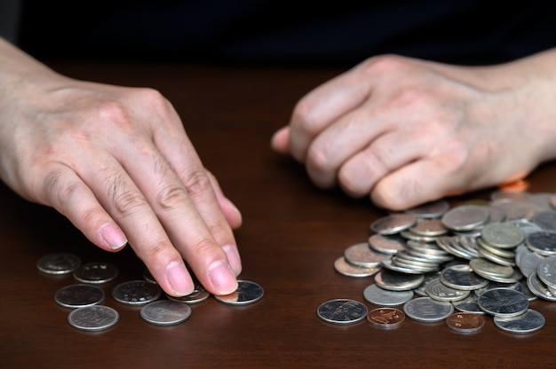 The hands of a man sorting stacked coins.