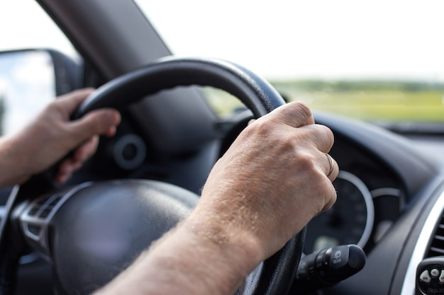 Hands of a man on the steering wheel of a car while driving in summer