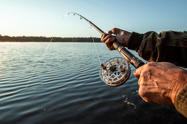 Hands of a man in a urp plan hold a fishing rod, a fisherman catches fish at dawn fishing hobby vacation