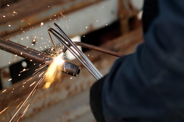 Hands of man, using argon welding to weld metal pipe, sparks flying in all directions