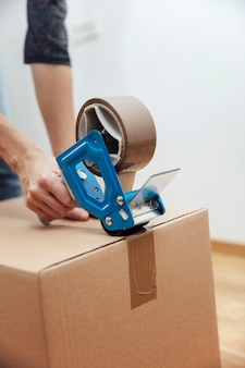 Hands of a man using a tape dispenser to seal a shipping box