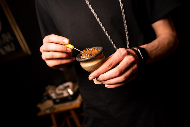 The hands of a man wearing a black t-shirt clog a hookah bowl with tobacco