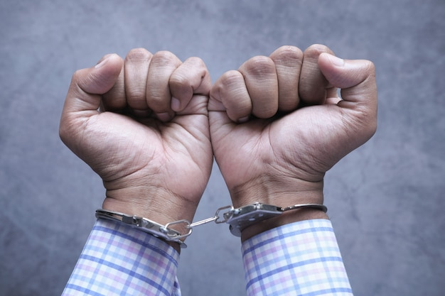 Hands of a man with handcuffs close up.