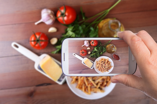 Hands of man with smartphone taking photo spicy penne pasta bolognese with vegetables,