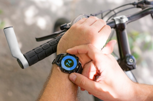 Hands of a man with a smartwatch in closeup while cycling