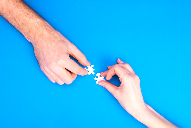 Hands of man and woman collect puzzles on a blue background  conceptual image of joint cooperation in the family. view from above