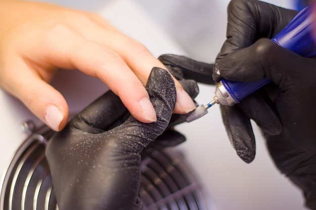 Hands of manicurist in black gloves and nails of client. woman in beauty salon.
