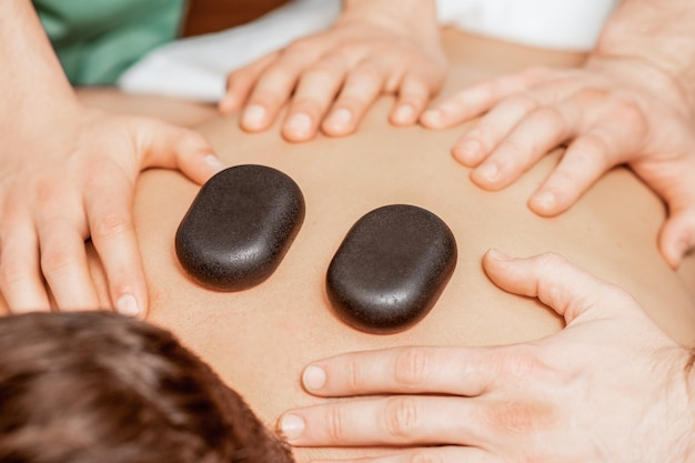 Hands of massage therapists doing back massage while hot stones on back of man close up in spa.