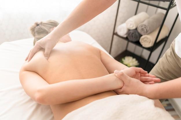 Руки массируют женское плечо