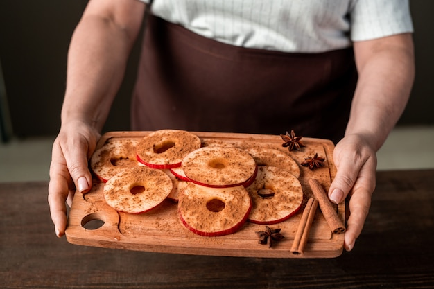 Hands of mature female holding chopping board with pile of fresh apple slices sprinkled with ground cinnamon over kitchen table