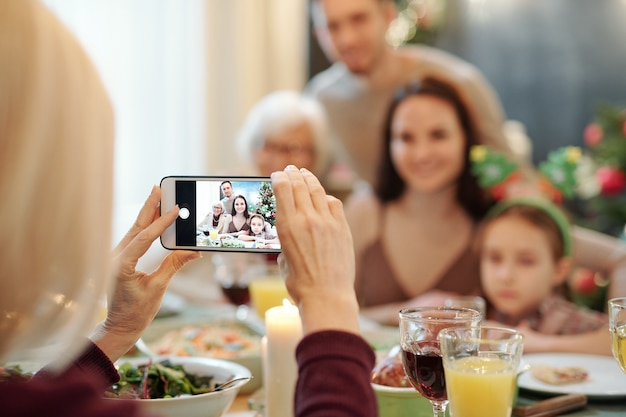Hands of mature female holding smartphone while taking photo of young couple, their little daughter and granny by dinner