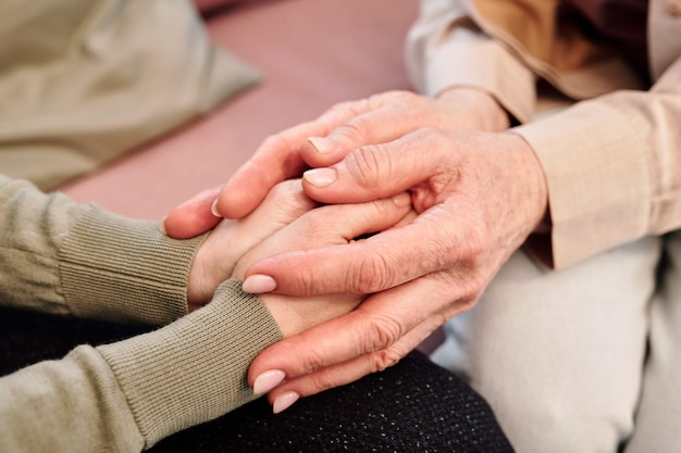 Hands of mature and young females during support