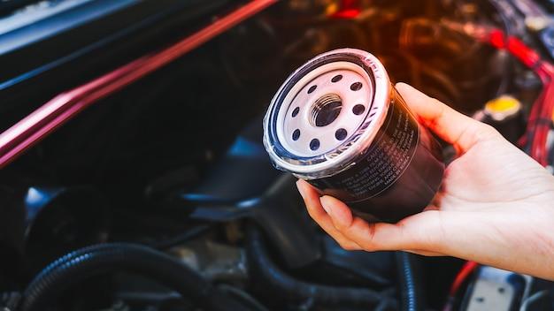 Механик руки делает сервисное обслуживание автомобиля замена масла и топливного фильтра
