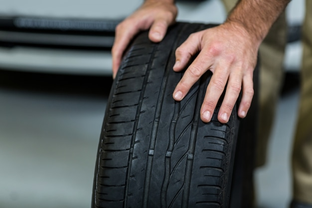 Hands of mechanic touching tyres