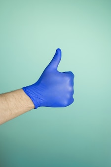 Hands in medical gloves on a blue wall. disease protection concept. pandemic protection concept. stop coronovirus. covid-19