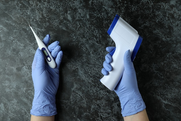 Hands in medical gloves hold digital thermometers on black smokey