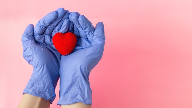 Hands in medical gloves hold the heart